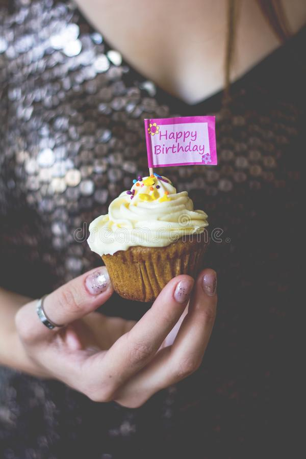 A woman holding a birthday cupcake in her hand. A woman holding a birthday cupcake with creamy topping in her hand stock images