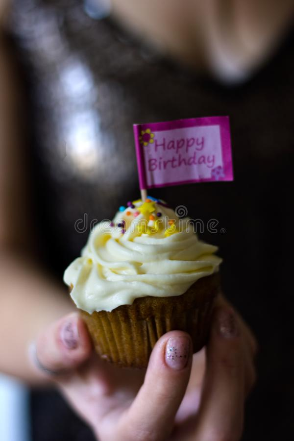 A woman holding a birthday cupcake in her hand. A woman holding a birthday cupcake with creamy topping in her hand royalty free stock image