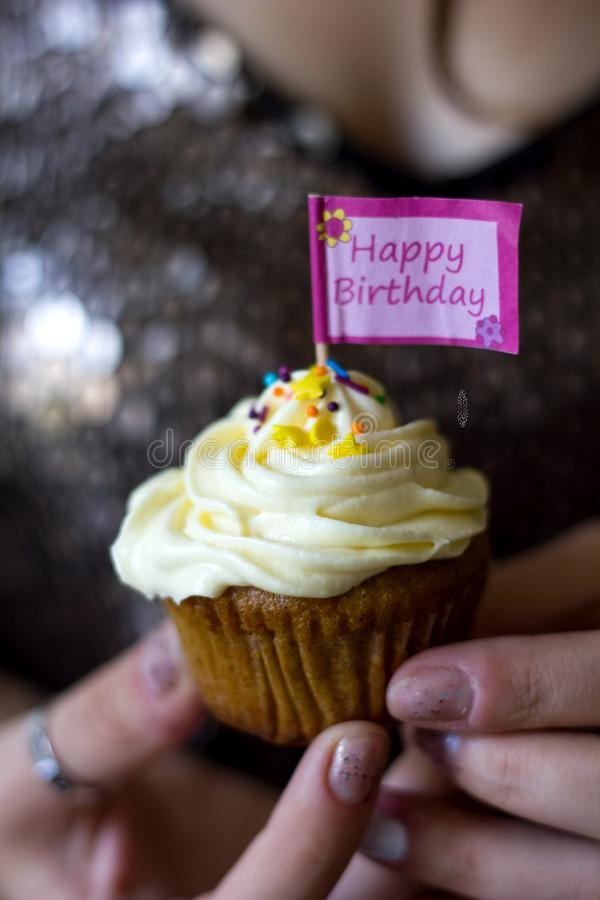 A woman holding a birthday cupcake in her hand. A woman holding a birthday cupcake with creamy topping in her hand royalty free stock images