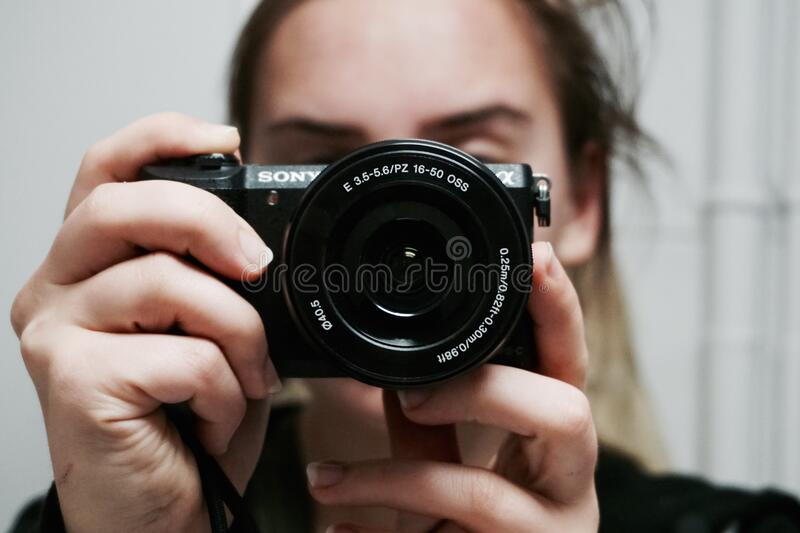 Woman Holding Black Sony Dslr Camera Taking a Photo of Herself at Mirror royalty free stock photo