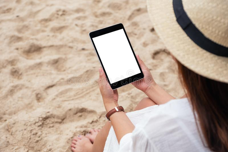 A woman holding a black tablet pc with blank desktop screen while sitting on a beach chair royalty free stock images