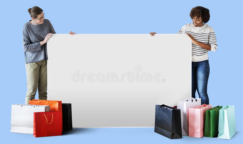 Woman holding on a blank board with shopping bags stock image