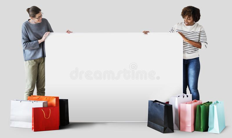 Woman holding a blank board with shopping bags royalty free stock image