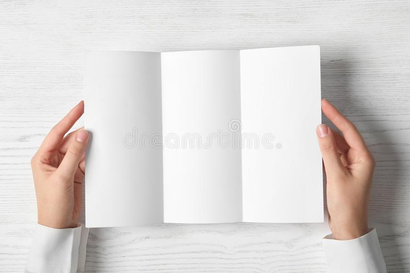 Woman holding blank brochure mock up on light background. Top view royalty free stock photo