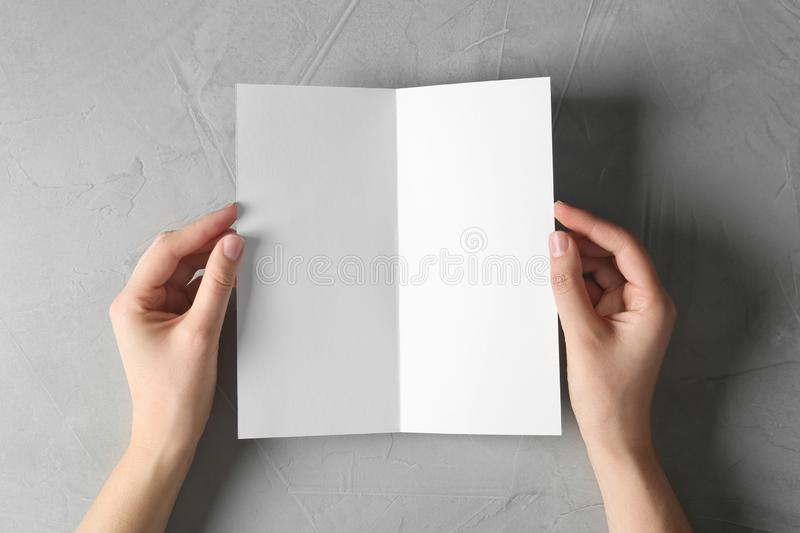 Woman holding blank brochure mock up on light background royalty free stock photography