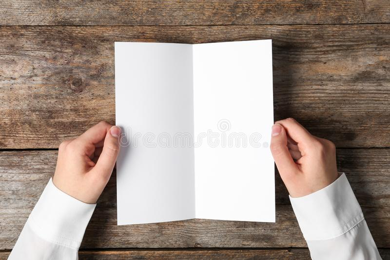 Woman holding blank brochure mock up on wooden table royalty free stock photography