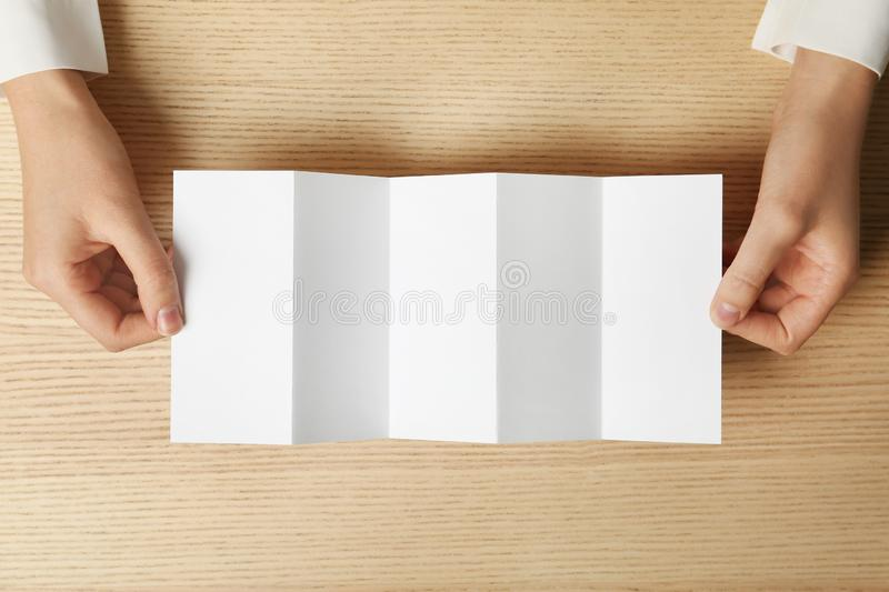 Woman holding blank brochure mock up on wooden table. Top view stock photo