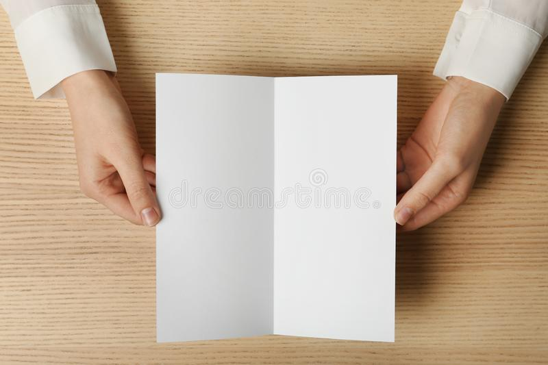 Woman holding blank brochure mock up on wooden table royalty free stock images