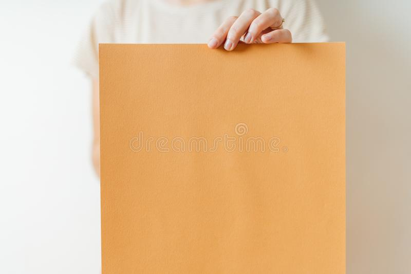 A woman holding blank orange paper poster or board. Indoors studio lifestyle stock image