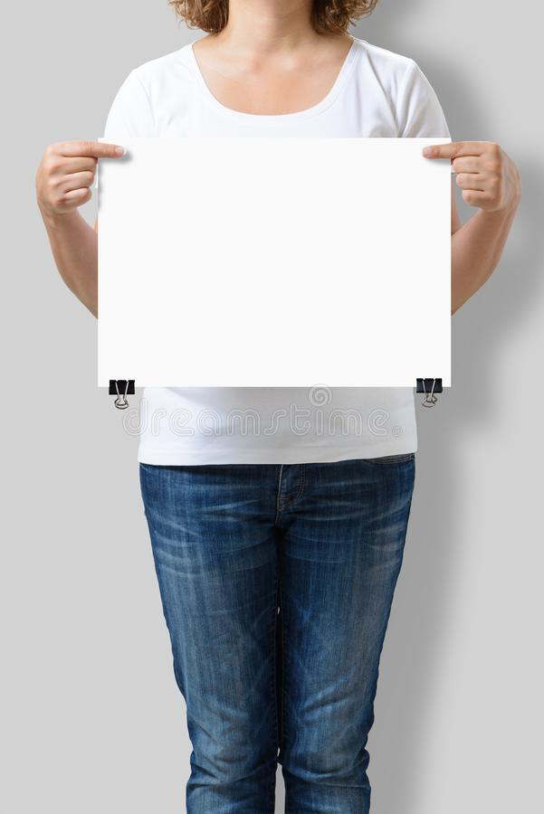 Woman holding a blank A3 poster mockup. royalty free stock photography