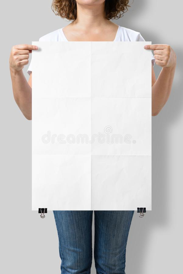 Woman holding a blank A2 poster mockup. royalty free stock photo