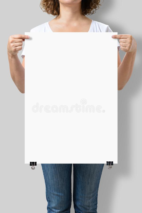 Woman holding a blank A2 poster mockup. stock images
