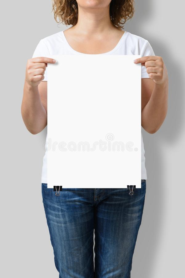 Woman holding a blank A3 poster mockup. royalty free stock photo