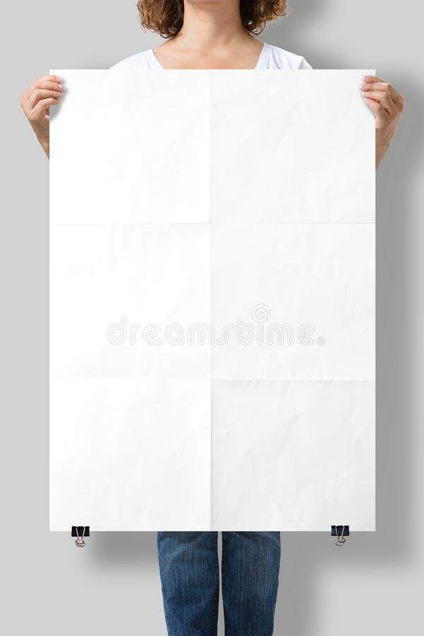 Woman holding a blank A1 poster mockup. Woman holding a blank A1 poster mockup isolated on a gray background stock image