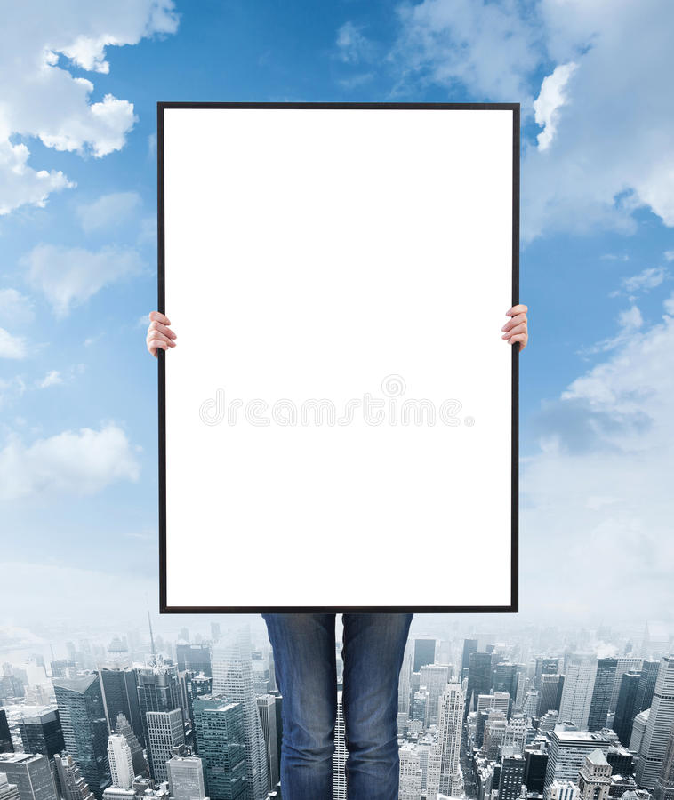 Woman holding a blank poster. Over city background royalty free stock photography