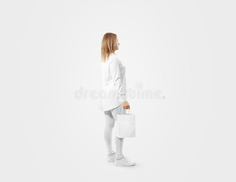Woman holding blank white craft paper bag design mockup. Person hold kraft textured purchase pack mock up isolated. Clear shop bagful branding template royalty free stock photo