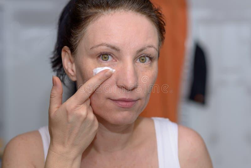 Woman holding a blob of moisturising cream stock image