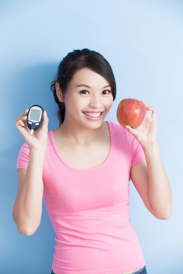 Woman holding blood glucose meter. Woman holding a blood glucose meter and apple to prevention diabetes isolated on blue background, asian royalty free stock photo