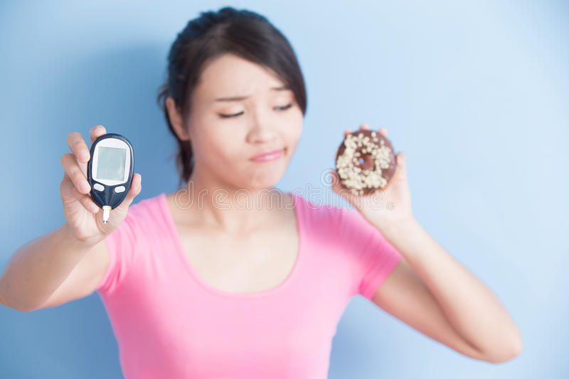 Woman holding blood glucose meter. Woman holding a blood glucose meter and donut to prevention diabetes isolated on blue background, asian stock photo