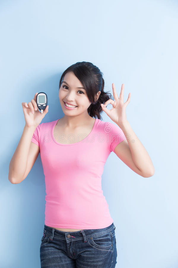 Woman holding blood glucose meter. Woman holding a blood glucose meter to prevention diabetes isolated on blue background, asian stock image