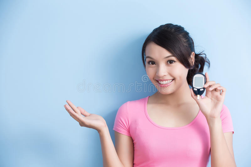 Woman holding blood glucose meter. Woman holding a blood glucose meter to prevention diabetes and show something isolated on blue background, asian stock photography