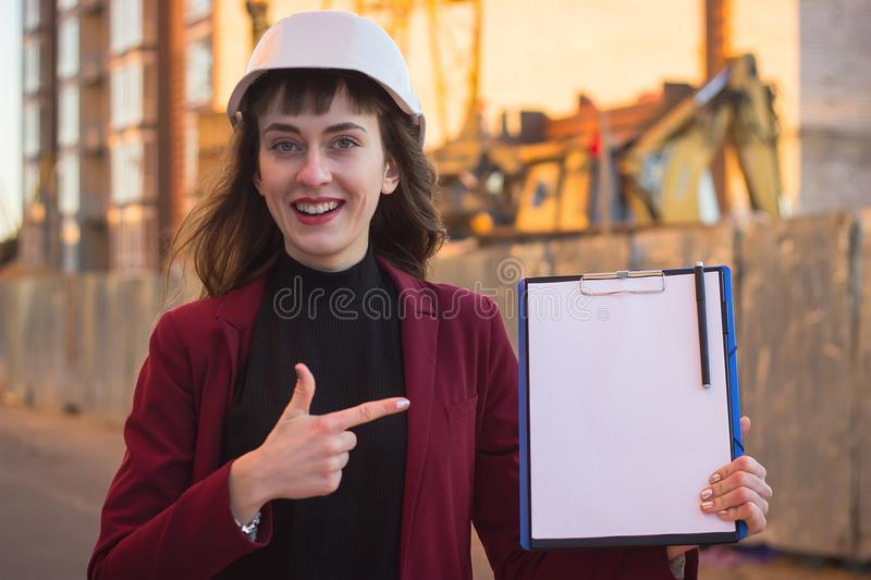 Woman holding blueprints, clipboard. Smiling architect in helmet at building stock photos