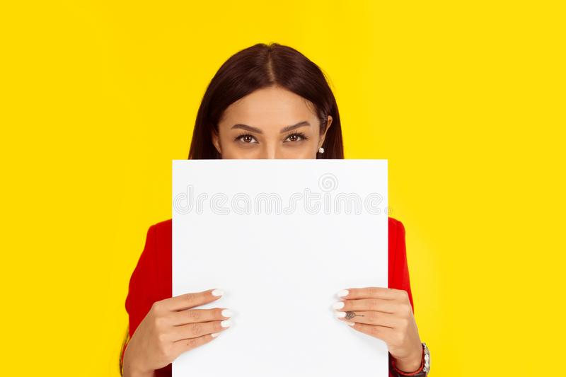 Woman holding a board paper hiding her smile behind it stock images