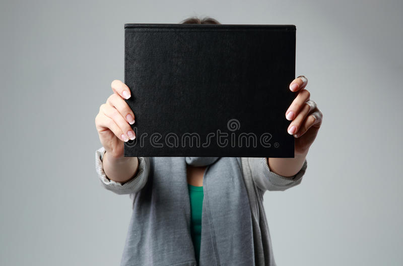 Woman holding a book and showing blank black cover. On gray background stock image