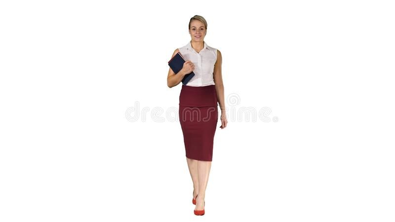 The woman holding the books walking to the camera on white background. royalty free stock image