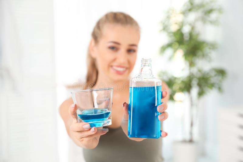 Woman holding bottle and glass with mouthwash stock images
