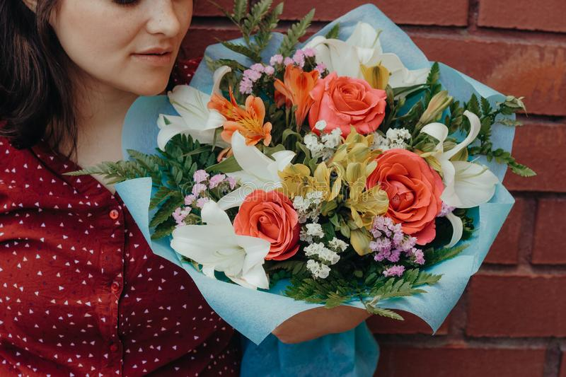 Woman holding bouquet of flowers against brick wall. Woman  holding bouquet of   flowers against brick wall film toned royalty free stock photography