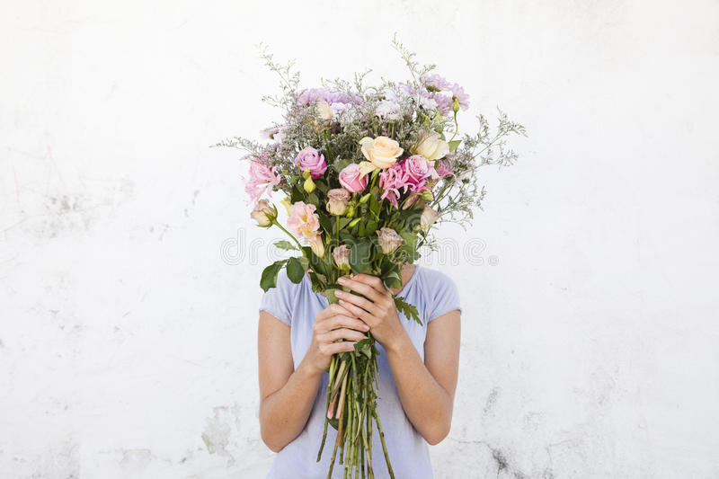 Woman holding bouquet of flowers. Young woman holding bouquet of flowers covering her face royalty free stock photos