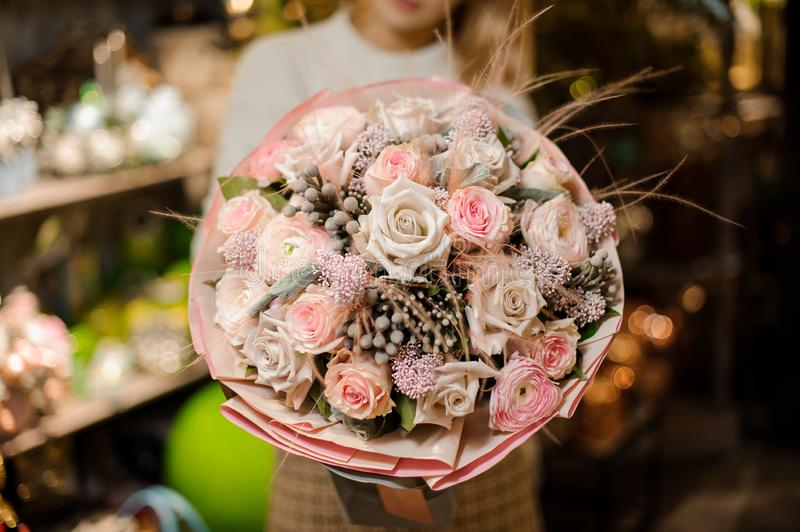 Woman holding a bouquet of pink and beige color roses with a decor of feathers and dry berries. In the background of flower shop stock images