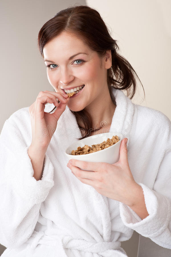 Woman holding bowl with cereals for breakfast. Happy woman in bathrobe holding bowl with cereals for breakfast royalty free stock image