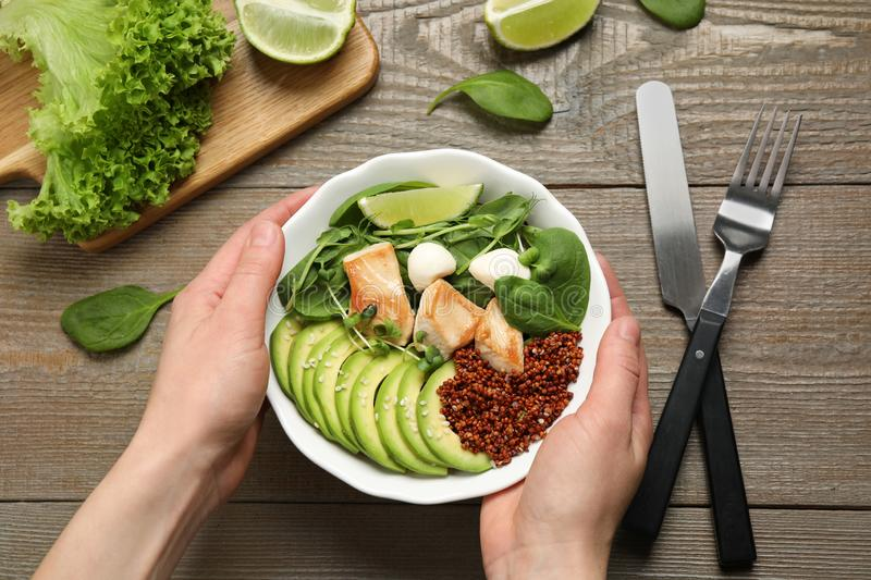 Woman holding bowl of delicious avocado salad with chicken at wooden table royalty free stock photos