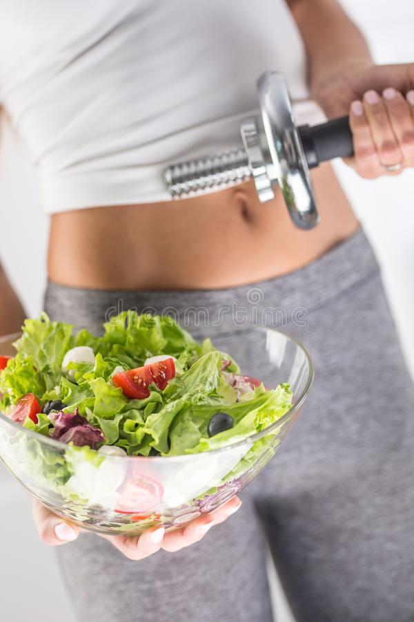 Woman holding bowl from fresh vegetable salad and dumbbell. stock images