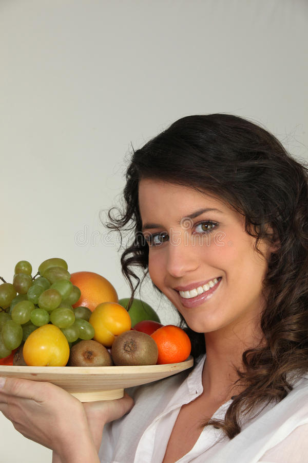 Woman holding a bowl of fruit stock photo