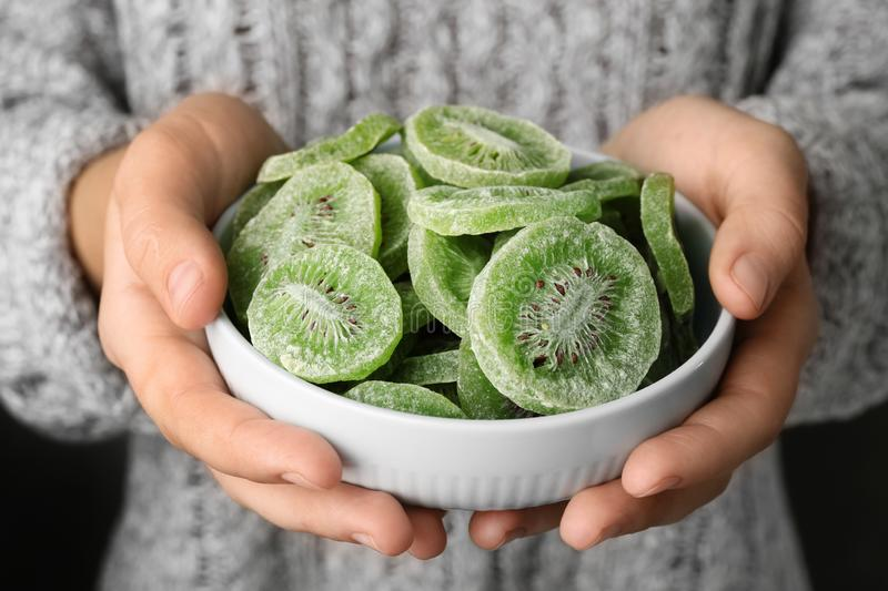 Woman holding bowl with slices of tasty kiwi. Dried fruit as healthy food royalty free stock photos