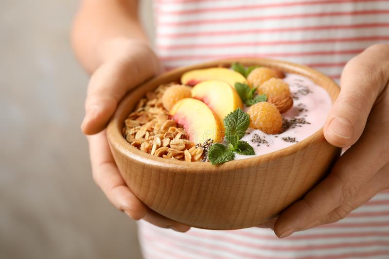 Woman holding bowl of tasty homemade granola with yogurt. Healthy breakfast. Woman holding bowl of tasty homemade granola with yogurt, closeup. Healthy breakfast stock images