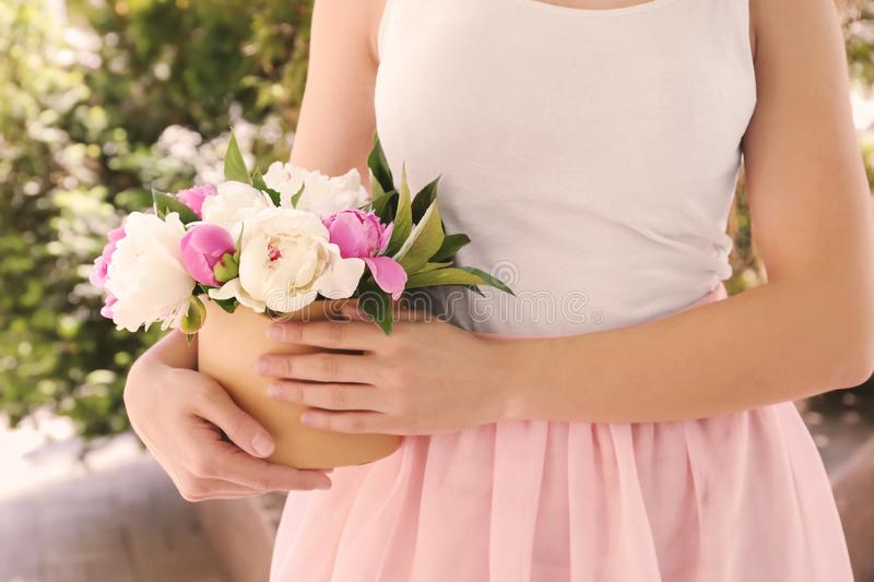 Woman holding box with beautiful peony flowers outdoors, closeup royalty free stock photos