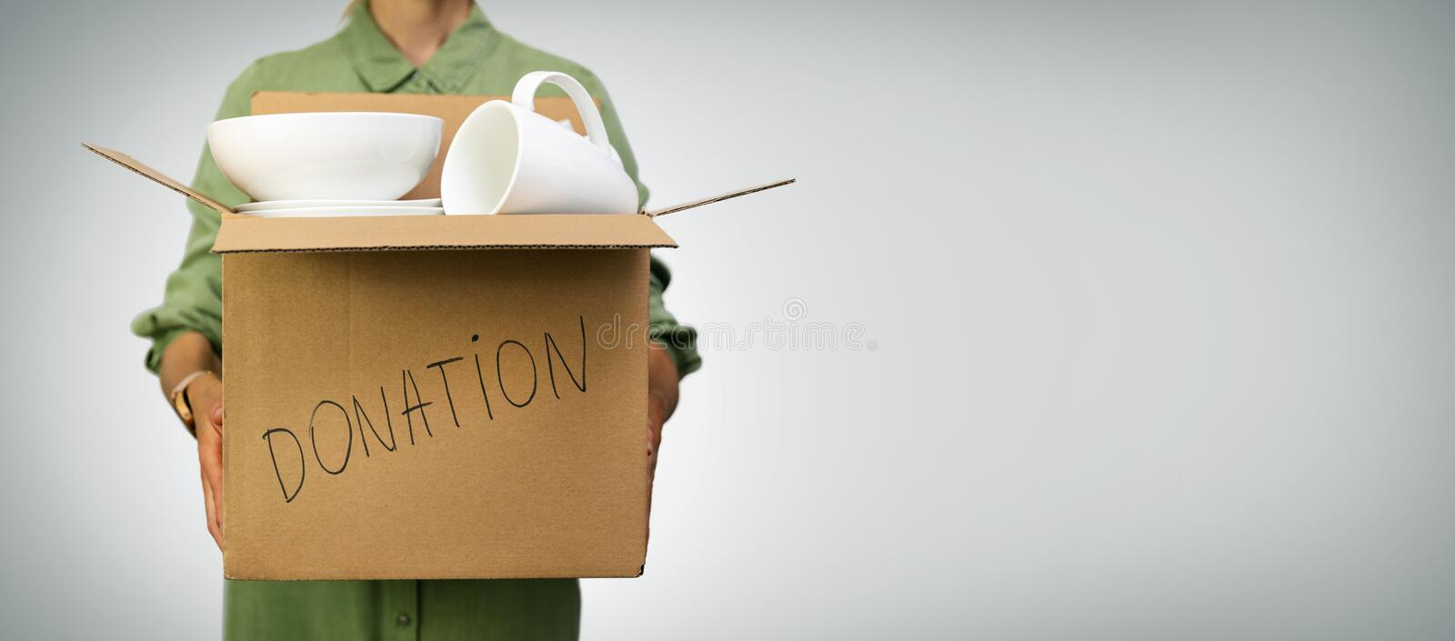 Woman holding box with household items for donations on gray background. With copy space stock images