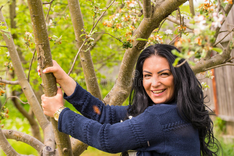 Woman holding branch tree. Happy woman in garden holding branch spring tree royalty free stock images