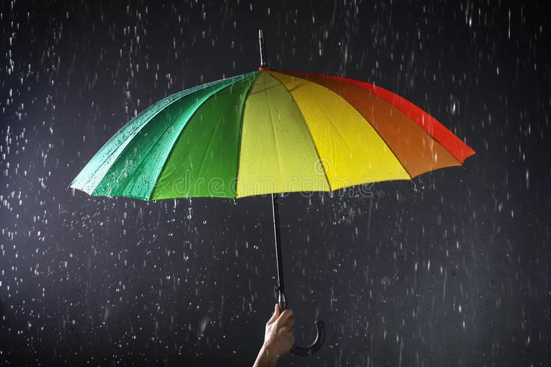 Woman holding bright umbrella under rain on dark background. Closeup stock photos