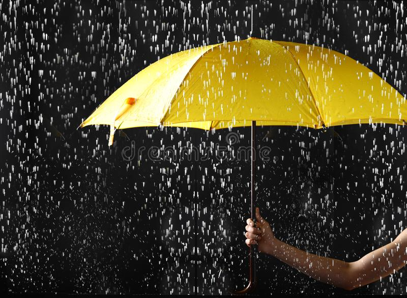 Woman holding bright umbrella under rain on dark background. Closeup stock image