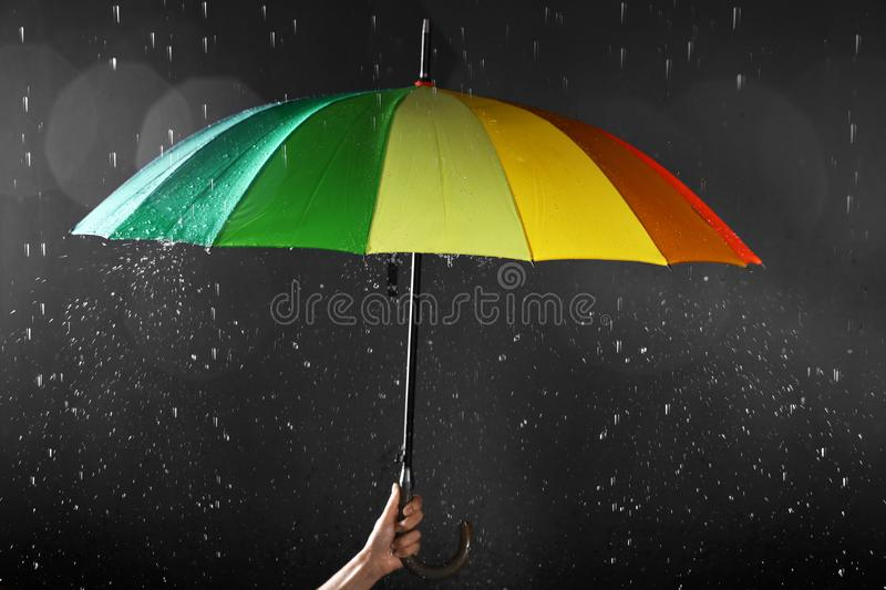 Woman holding bright umbrella under rain on dark background,. Closeup stock photos