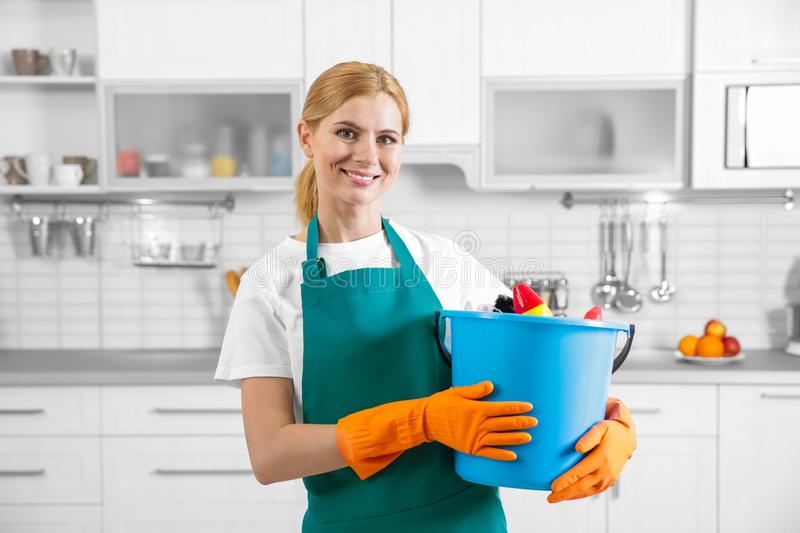 Woman holding bucket with cleaning agents. At home stock photography