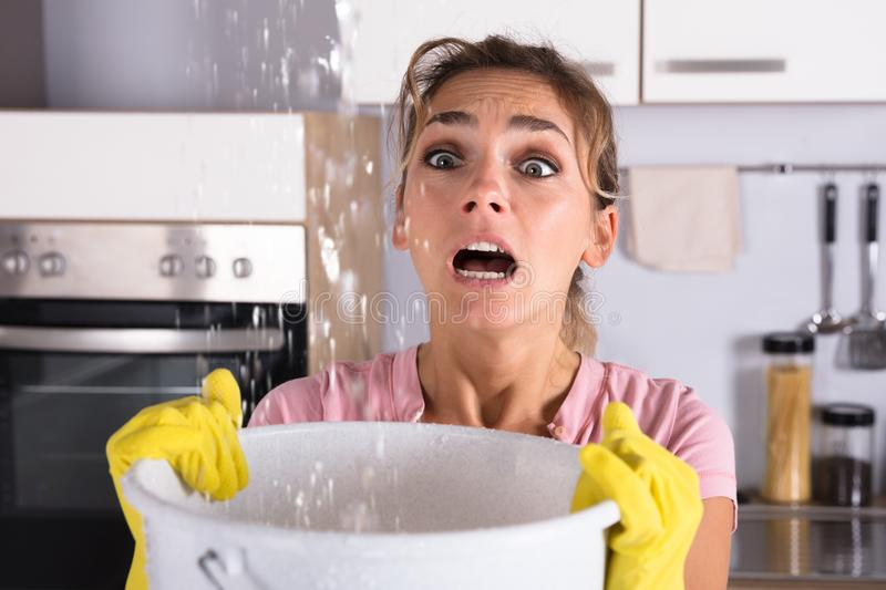 Woman Holding A Bucket While Water Droplets Leak From Ceiling stock photos