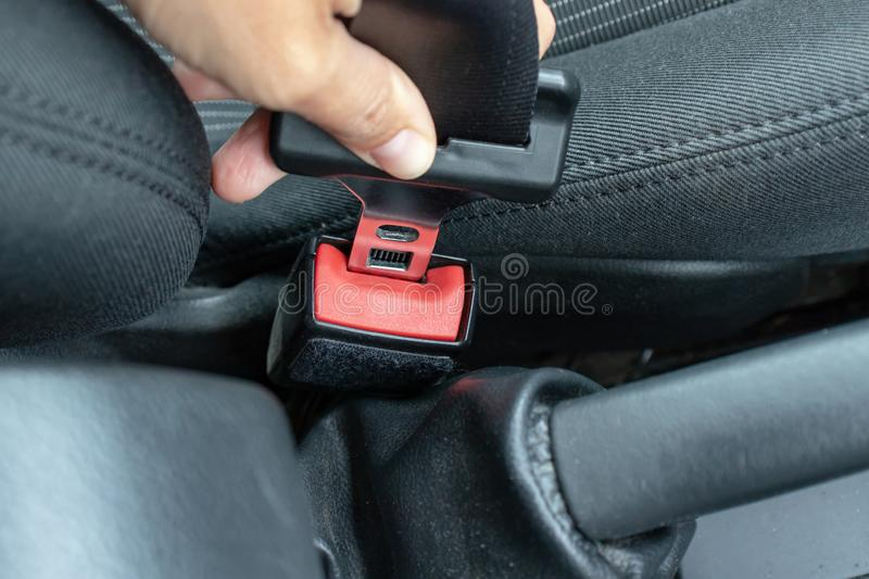Woman holding a buckle of a safety belt in hand and fastening a seatbelt, car safety and driver protection concept stock photos
