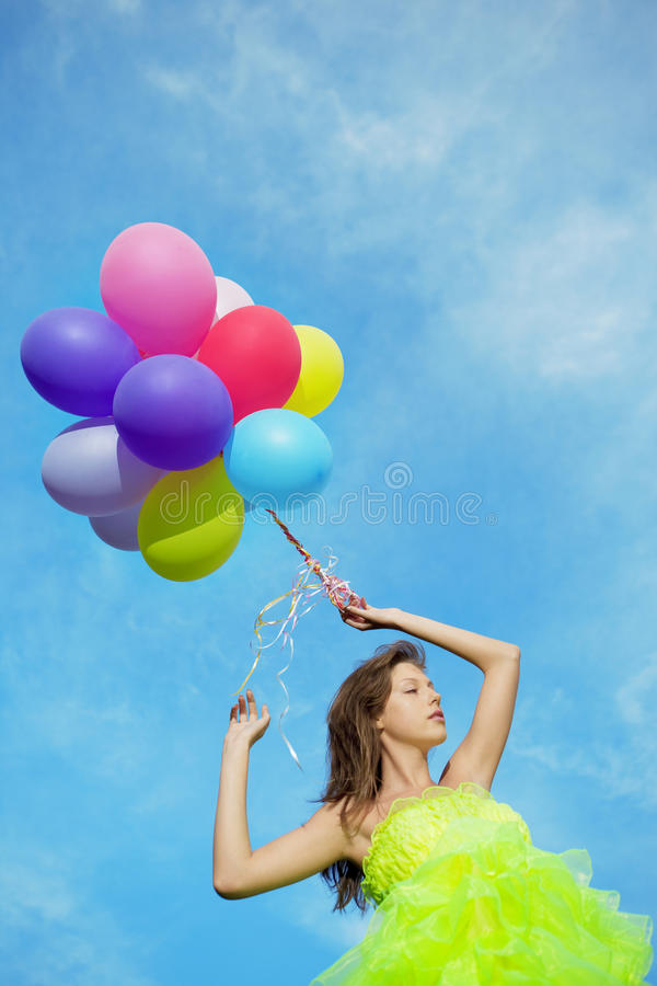 Woman holding bunch of colorful air balloons