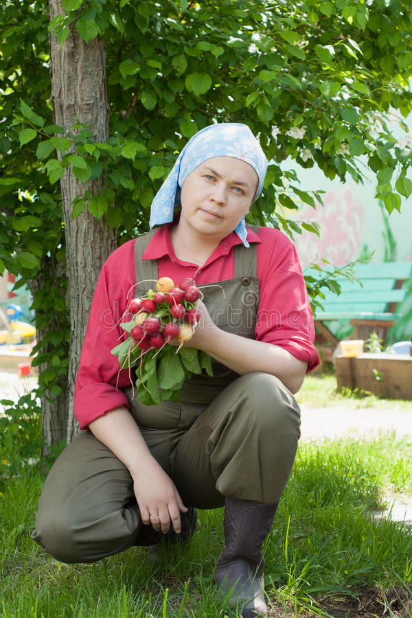 Woman holding a bunch of radishes royalty free stock photo